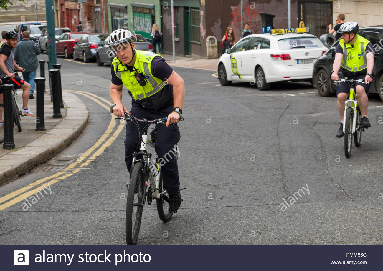 Gardaí­ officers on bicycle patrol wearing helmets and high visibility reflective vest, Fishamble Street, Christchurch, Dublin, Leinster, Ireland Stock Photo