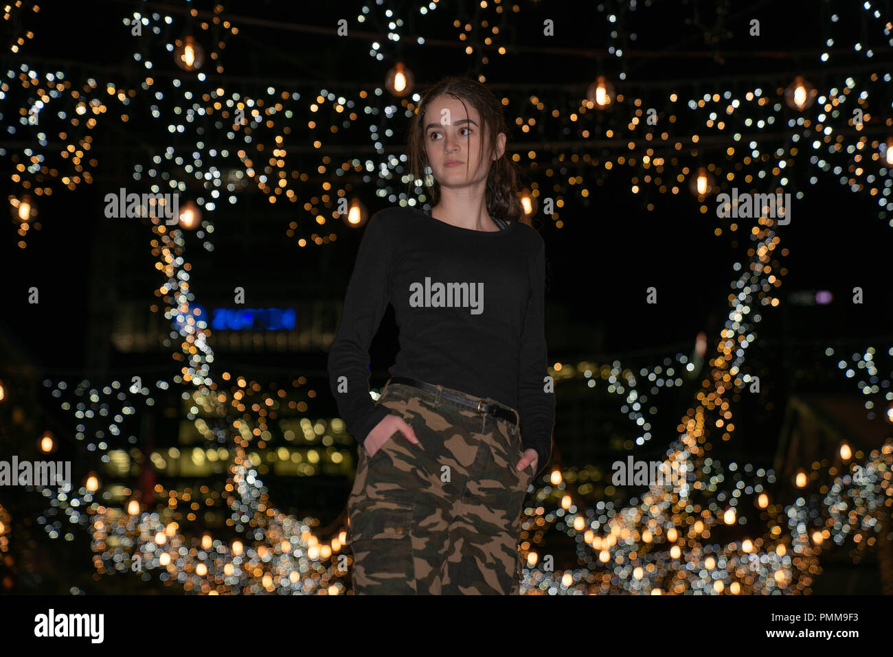 AUCKLAND, NEW ZEALAND - SEPTEMBER 14 2018; Young woman surrounded by decorative fairy lights.in Auckland's Britomart area bright and decorative lights Stock Photo