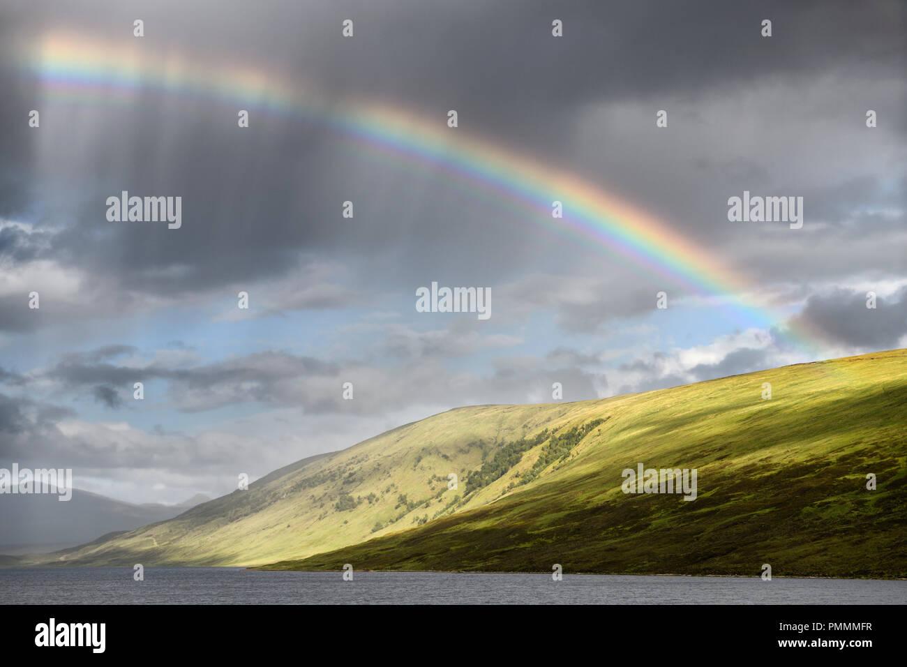Rainbow and dark clouds over Loch a Chroisg ending at An Liathanach Hill near Badavanich Scottish Highlands Scotland UK - Stock Image