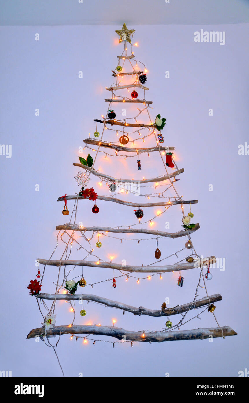 creative modern wall hanging christmas tree made of driftwood with lights and hanging decorations and baubles