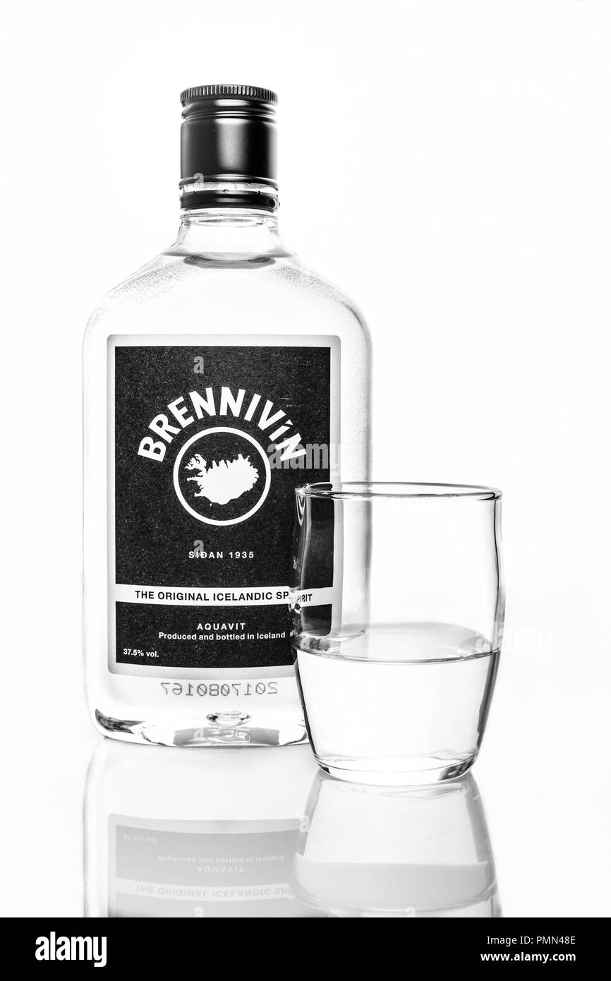 Bottle of Brennivin aquavit with shot glass against white background - Stock Image