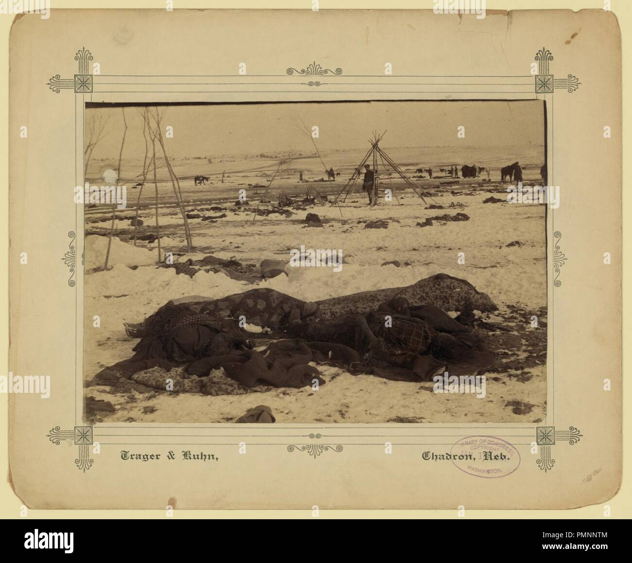 Big Foot's camp three weeks after the Wounded Knee Massacre (Dec. 29, 1890), with bodies of several Lakota Sioux people wrapped in blankets in the foreground and U.S. soldiers in the Stock Photo