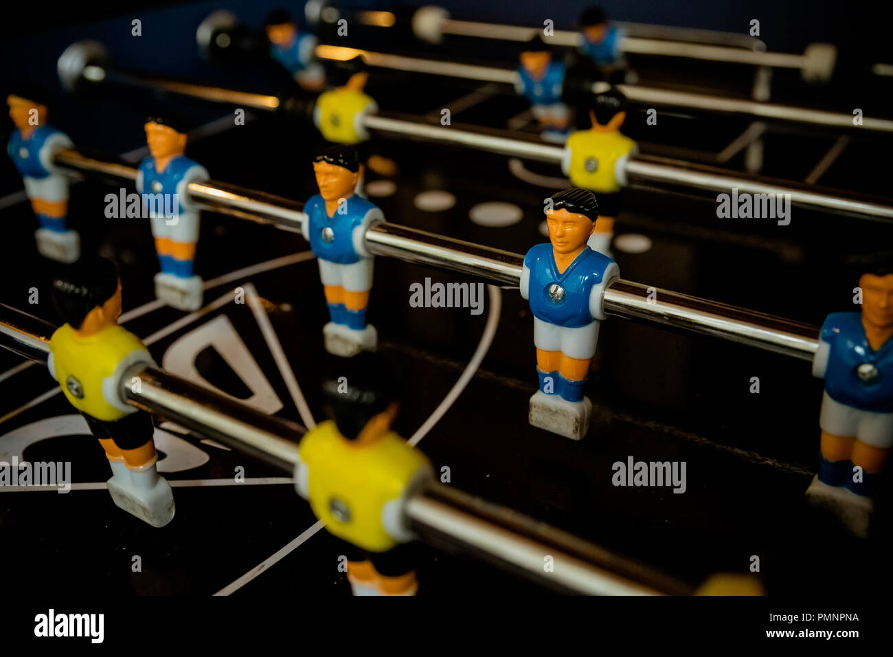 Table football game with yellow and blue players.Selective focus.able Football Game Hobby or Leisure.sport team football players.Enjoying Table Soccer Game Inside the Office During their Break Time. - Stock Image