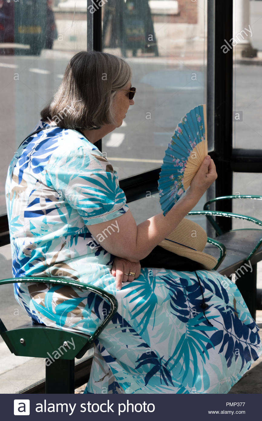 Older woman sits fanning herself whilst waiting for a bus during the 2018 heatwave, Blandford Forum, Dorset, England, UK - Stock Image