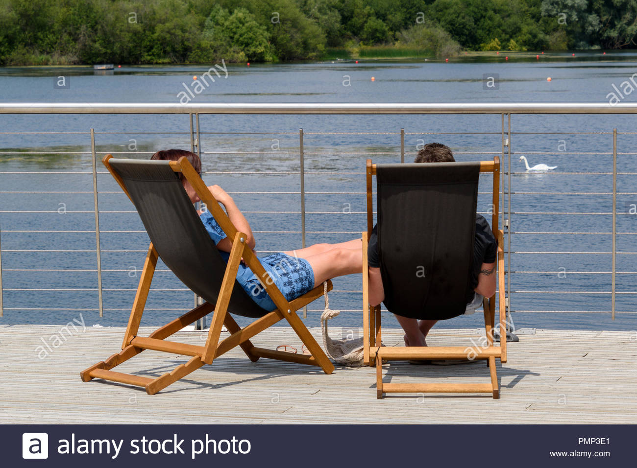 A young couple captured from behind sitting in deckchairs overlooking Rushden Lake, Northamptonshire, England, UK - Stock Image