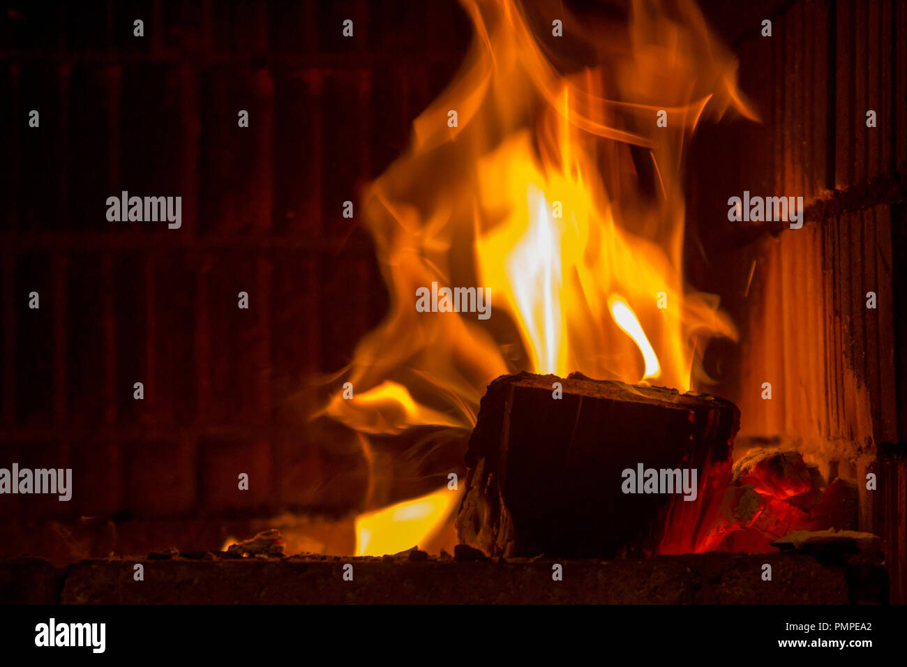 Firewood in blazing flames of the fireplace - Stock Image