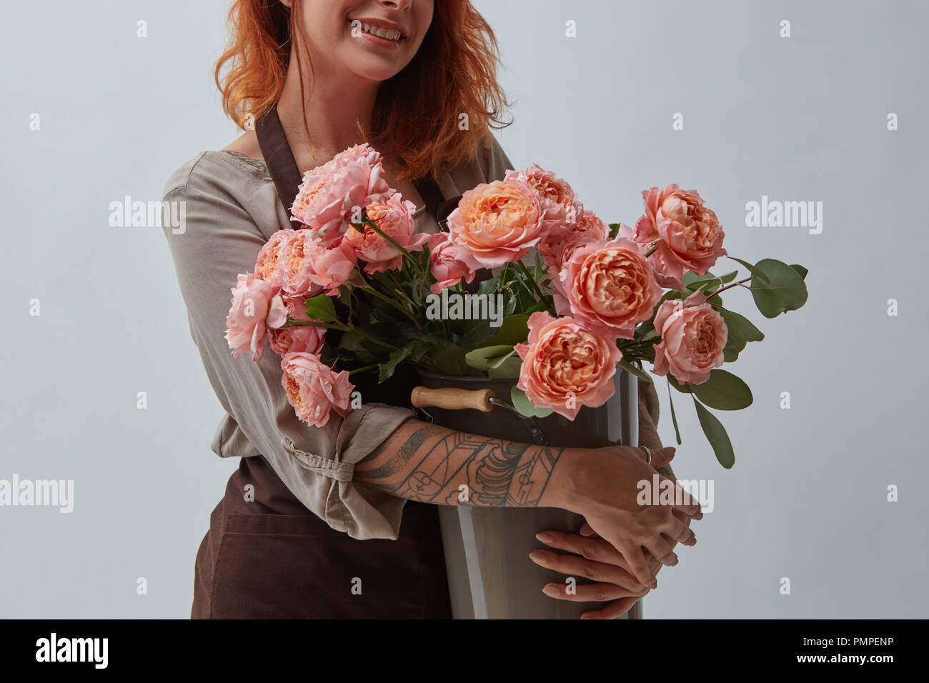 Young Red Haired Girl With A Tattoo Holding A Bouquet Of Pink Roses