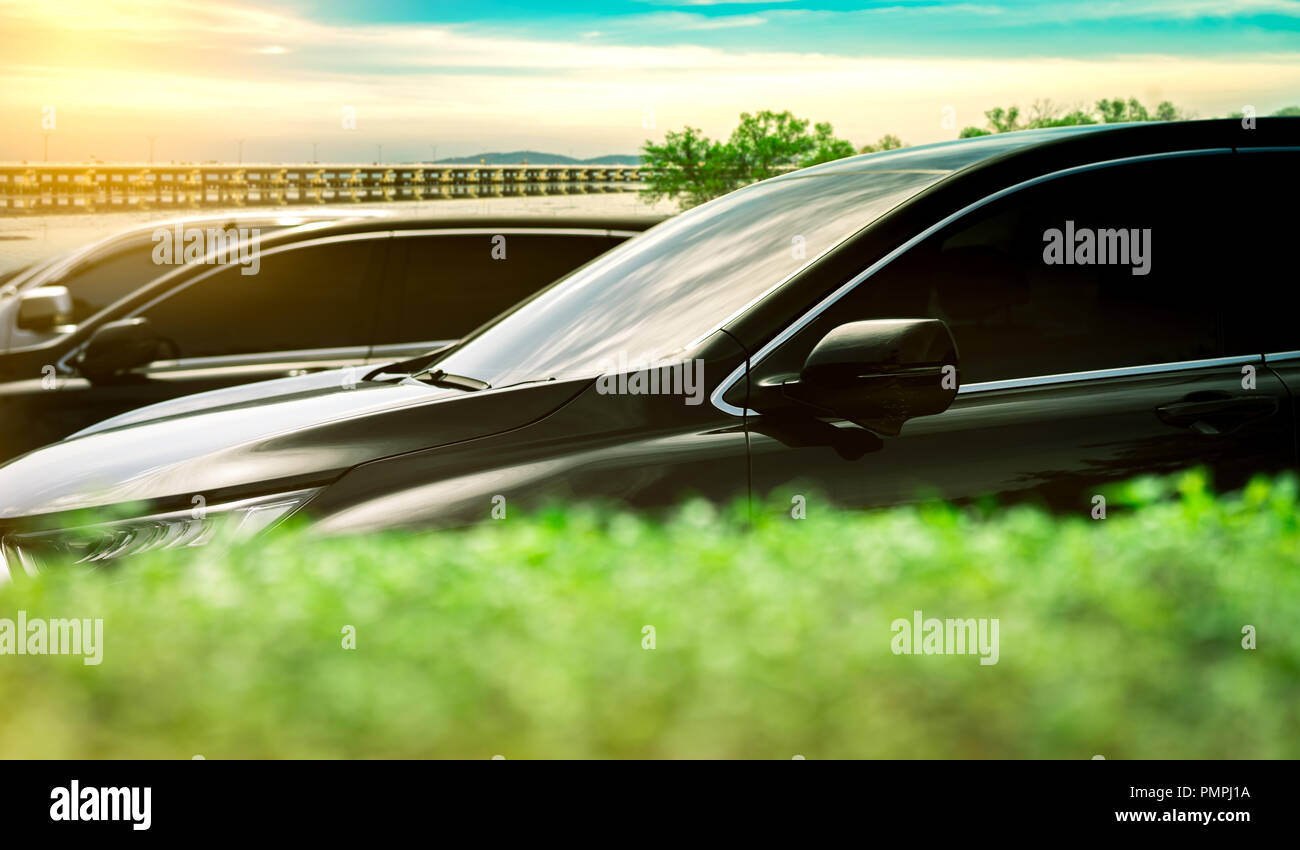 Luxury black shiny SUV Car parked on concrete parking area by the sea with blue sky, clouds, mountain and concrete bridge. Car stock for sale. Car par - Stock Image