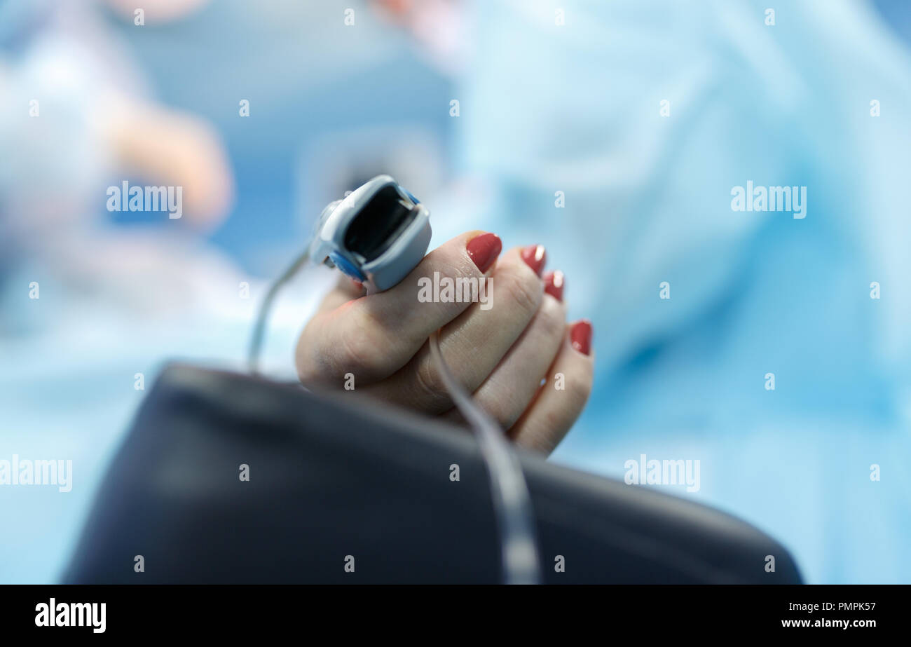 Patients hand with a sensor on the blurry background of the group of doctors in the operating room. Close up Stock Photo