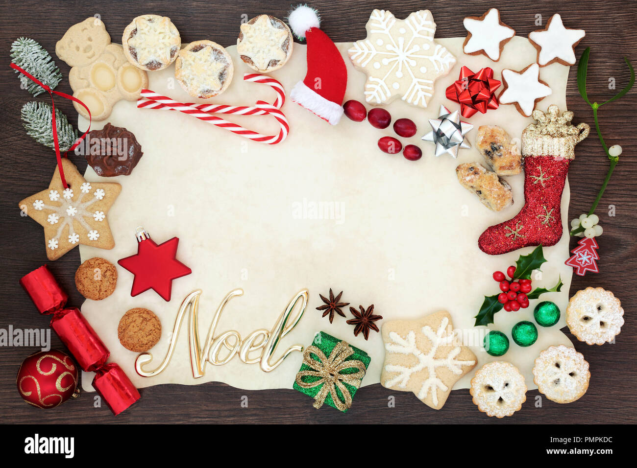 Christmas and noel background border including tree decorations, biscuits, cakes, fruit, chocolates and winter flora on parchment paper on rustic oak. - Stock Image