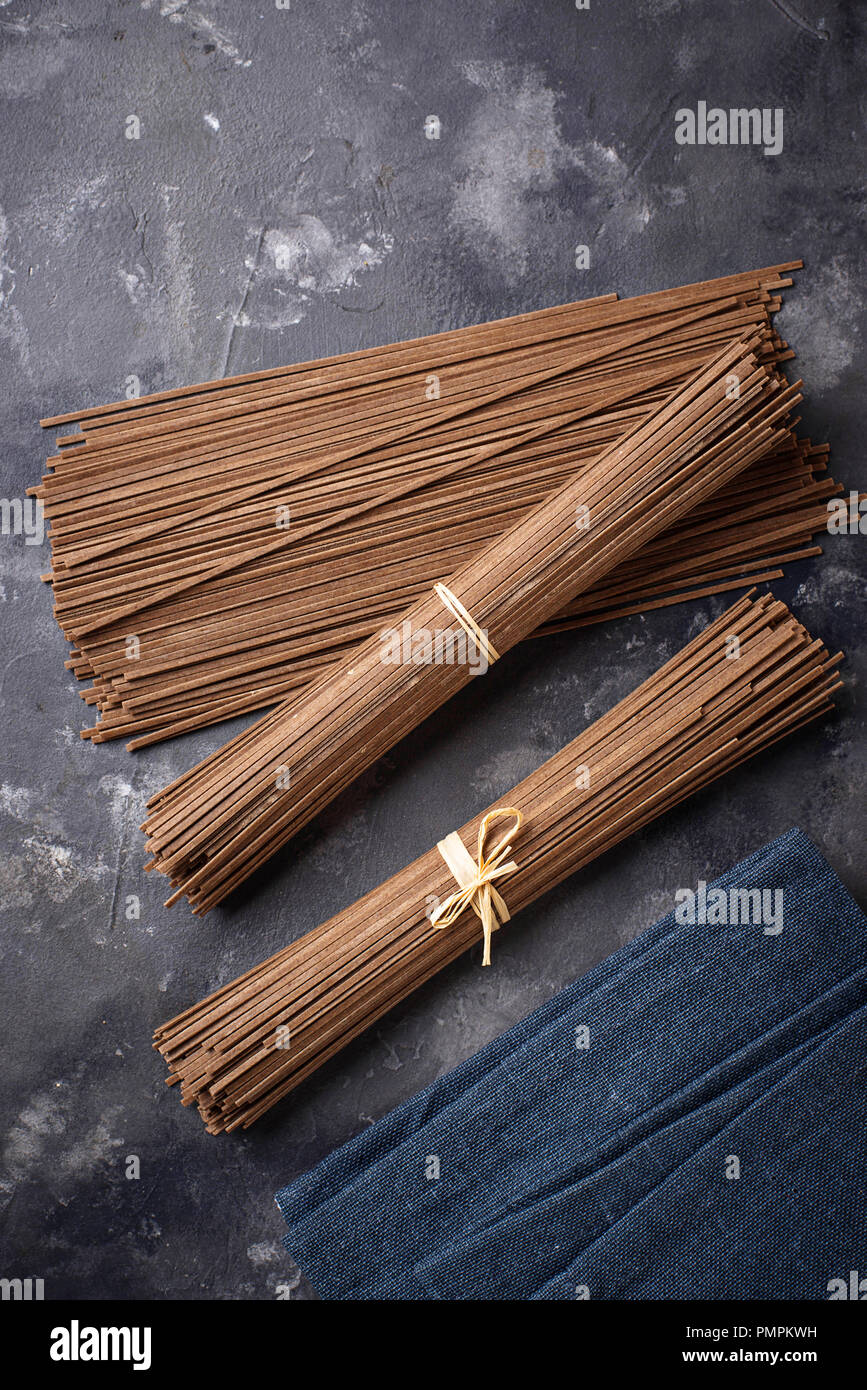 Raw uncooked Japanese soba noodles on grey bacground - Stock Image