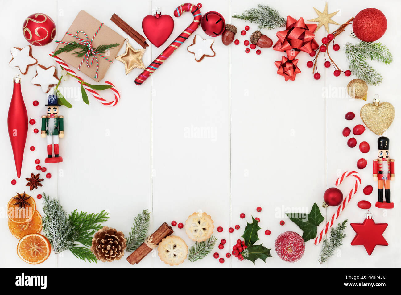 Christmas background border composition with traditional symbols of bauble decorations, candy canes, mince pies, fruit, spices, winter flora and gift  - Stock Image