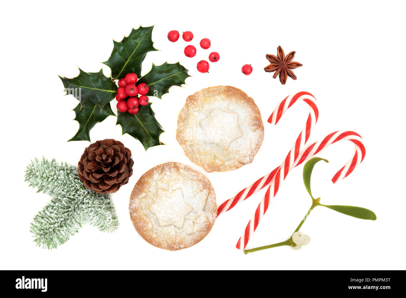 Christmas symbols with mince pie tarts, winter flora of holly, snow covered fir, pine cone, candy canes and star anise on white background. Top view. - Stock Image