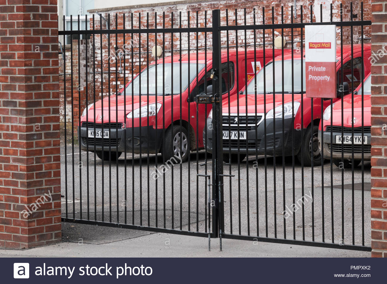 Looking through locked gates to a Royal Mail Private Property parking yard, Bridport, Dorset, England, UK - Stock Image