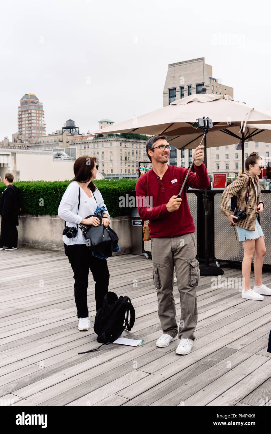 New York City, USA - June 23, 2018: Couple taking selfies with stick at the rooftop of Metropolitan Museum of Art in New York Stock Photo