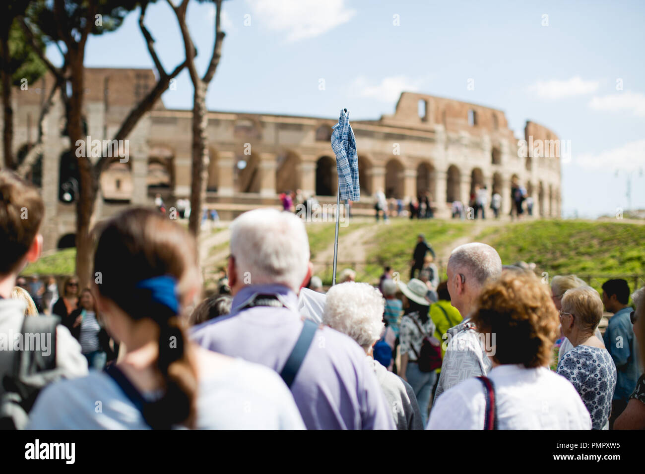 A group of tourists lead by a tour guide in front of the Colosseum / Coliseum in Rome - Stock Image