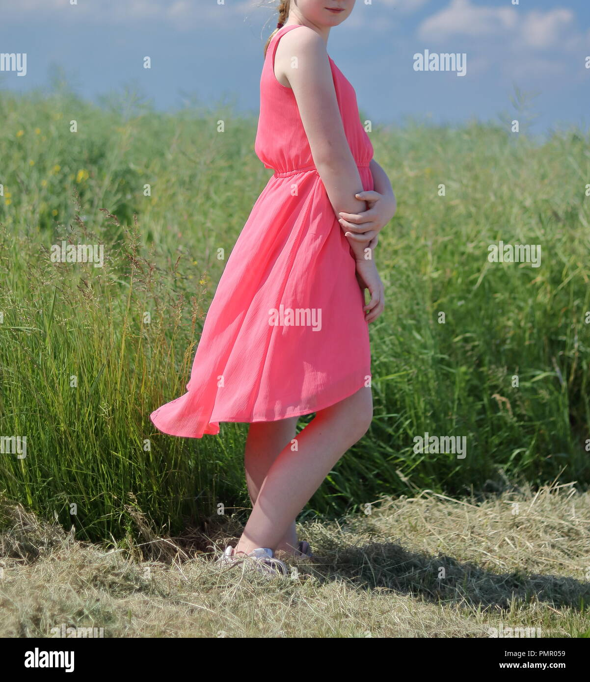 Young pretty girl (teenager, woman) stnads alone in green meadow, dressed in sleeveless pink summer dress, a bit windy. - Stock Image