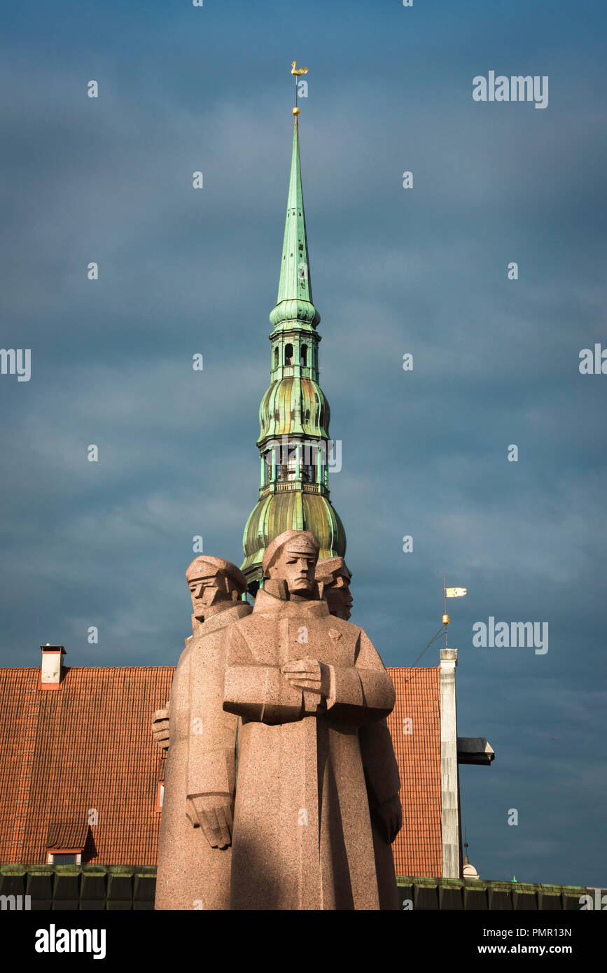 View of the Latvian Riflemen Monument against the backdrop of the roof of the House Of The Blackheads and St Peter's Church spire, Riga, Latvia. - Stock Image