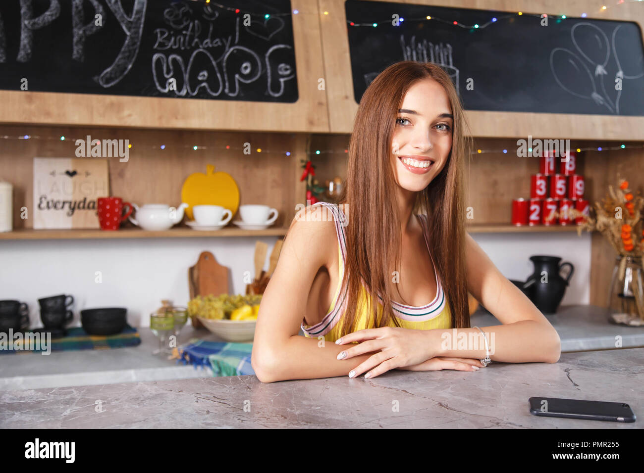 Portrait of young long hair housewife at the light modern kitchen - Stock Image