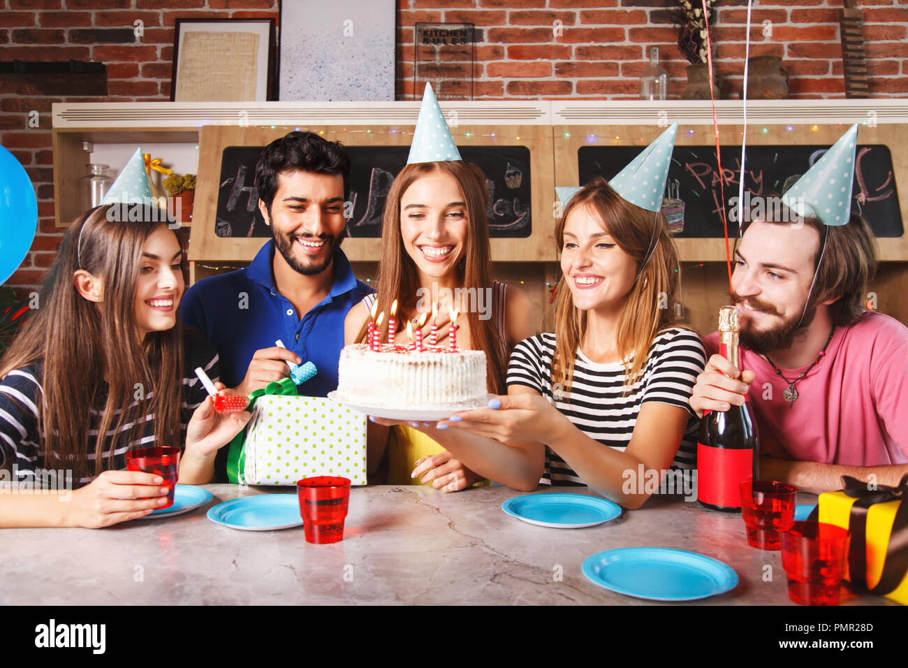 Excited woman ready to blow out candles on white frosting cake on table at birthday party with happy friends - Stock Image