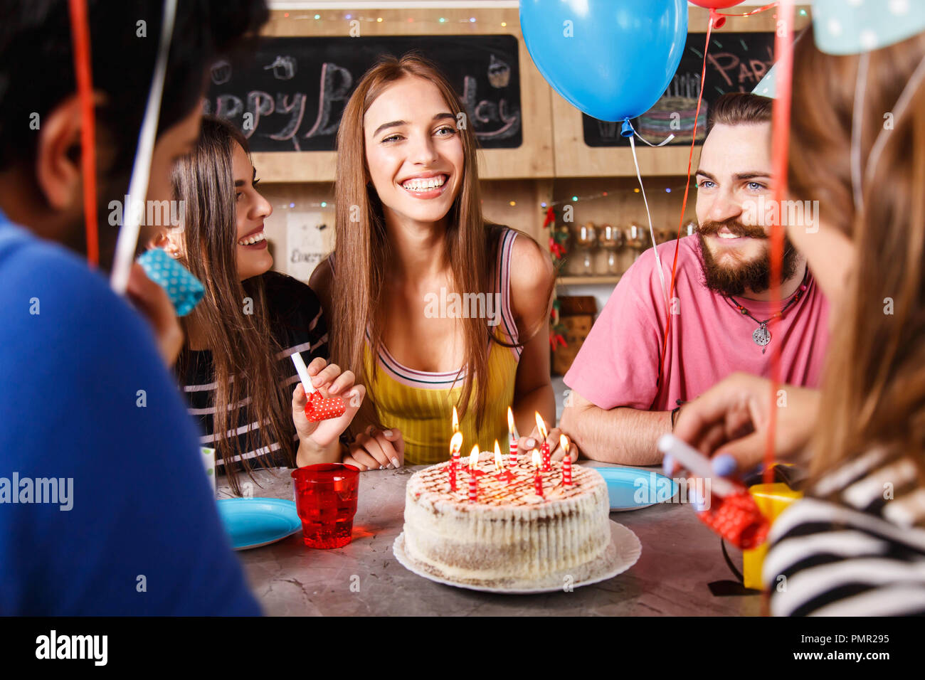 Brunette long hair girl sitting around her friends and smiling a lot on a birthday party - Stock Image