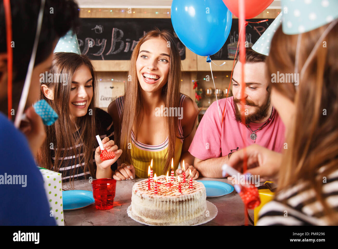 Five young adults celebrating a birthday party as they sitting around a table with cake and party hats - Stock Image