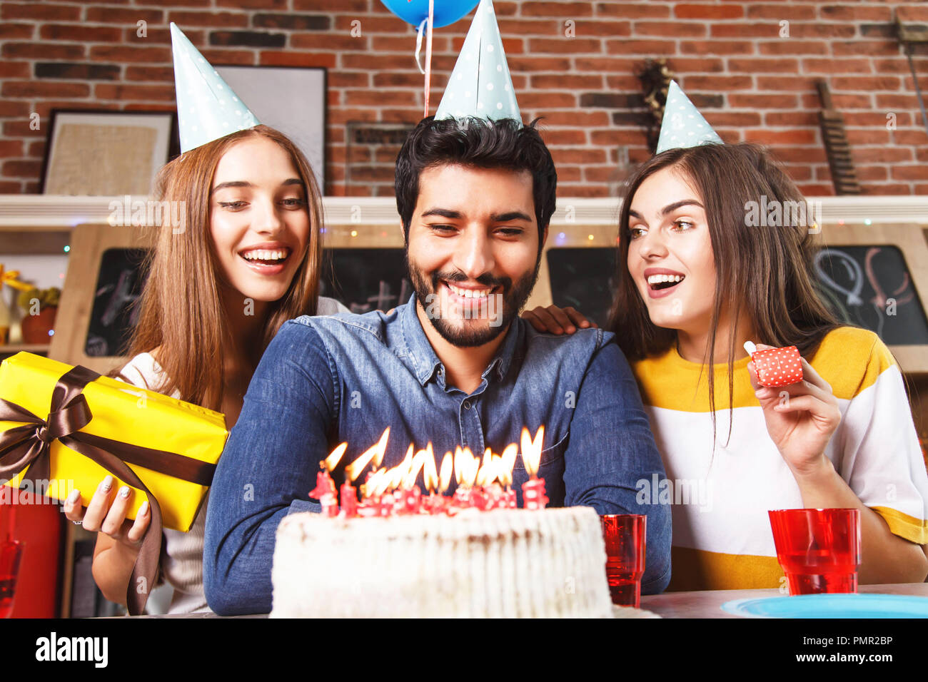 Happy bearded man ready to blow out candles on the white cake at birthday party with his girlfriends - Stock Image