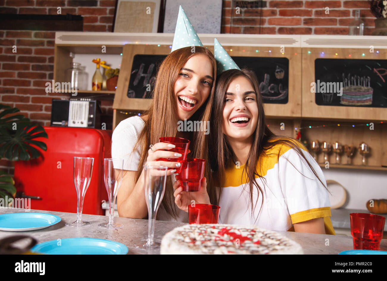 Brunette girlfriends in the party hats holding drinks and celebrating birthday - Stock Image