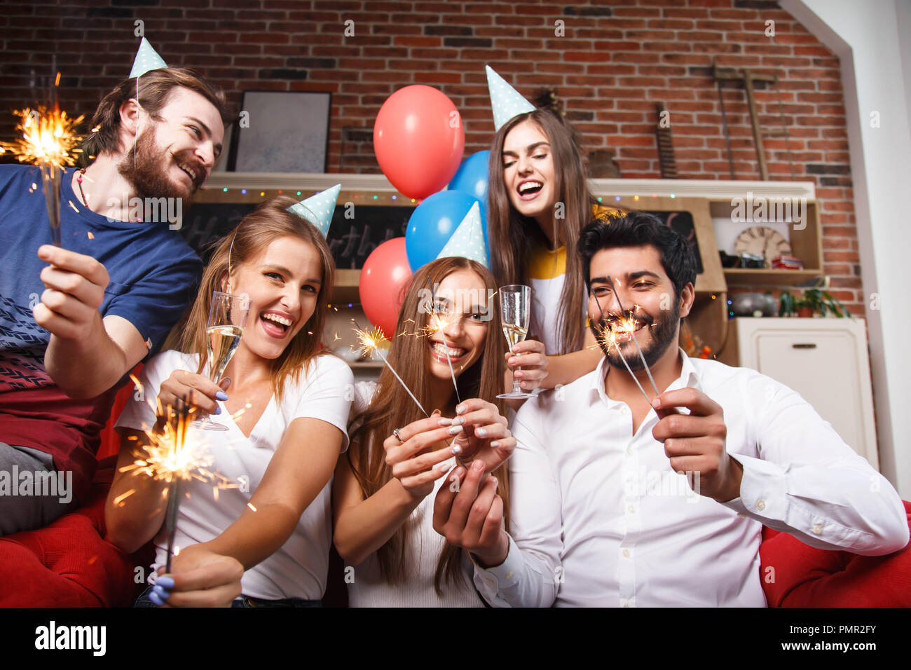 Cheerful group of friends holding sparklers and having fun on the sofa - Stock Image