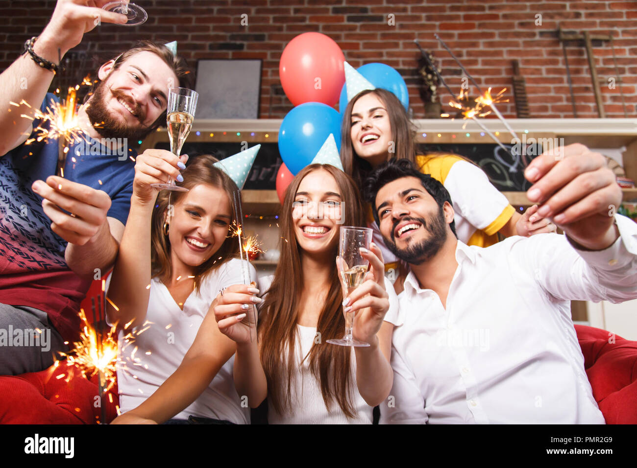 Happy people raising glases with champagne and holding sparklers while sitting on the sofa - Stock Image