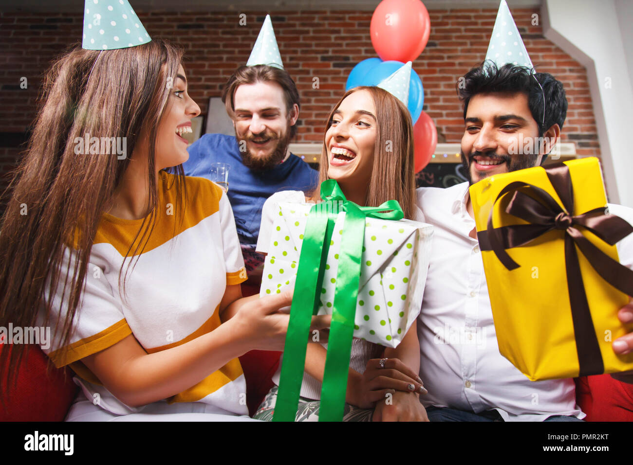 Friends offering gifts to amazing woman in a party hat, they are smiling and laughing a lot - Stock Image