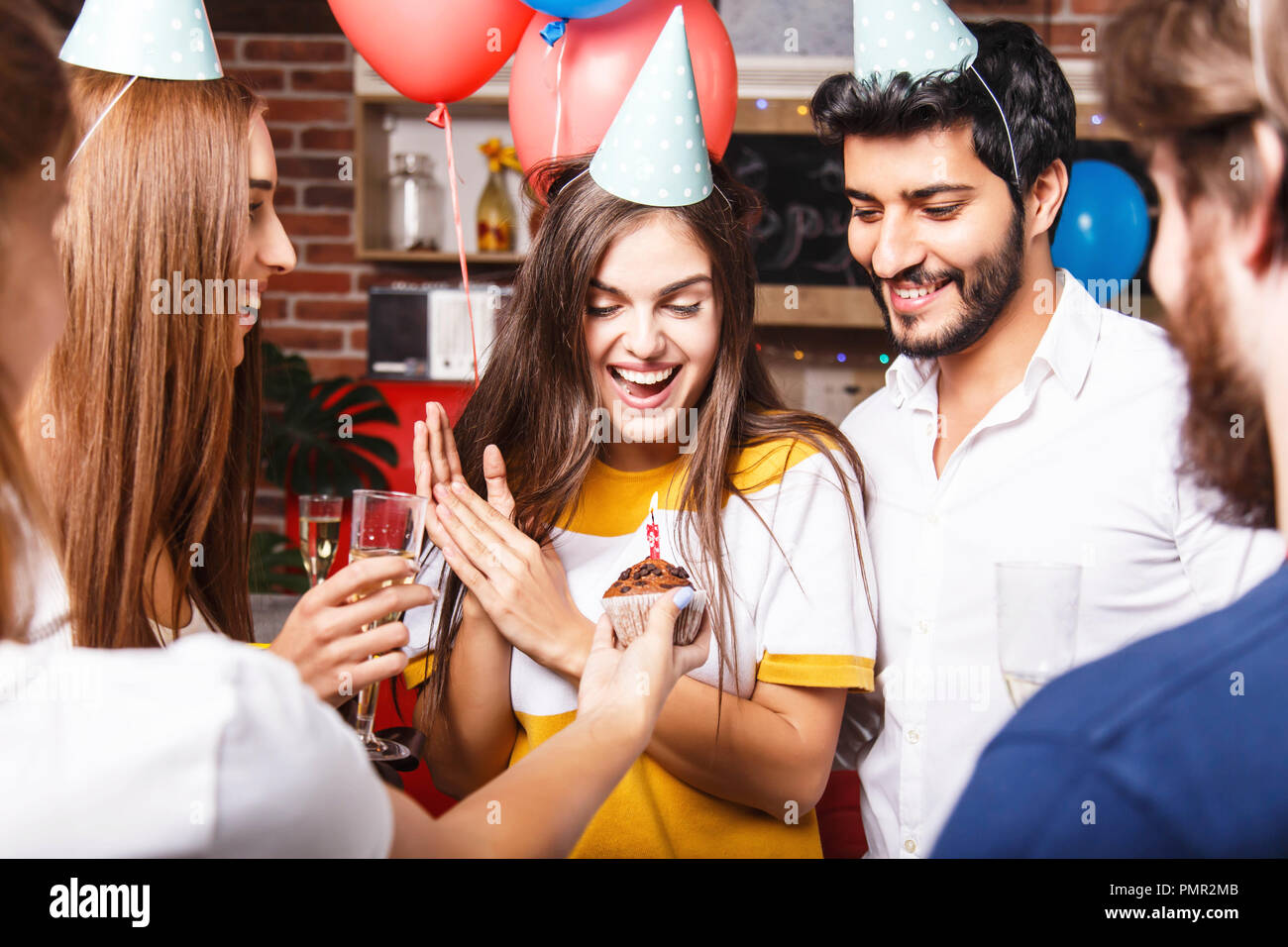 Friends congratulates brunette birthday girl in party hat with cupcake, she feeling surprised - Stock Image