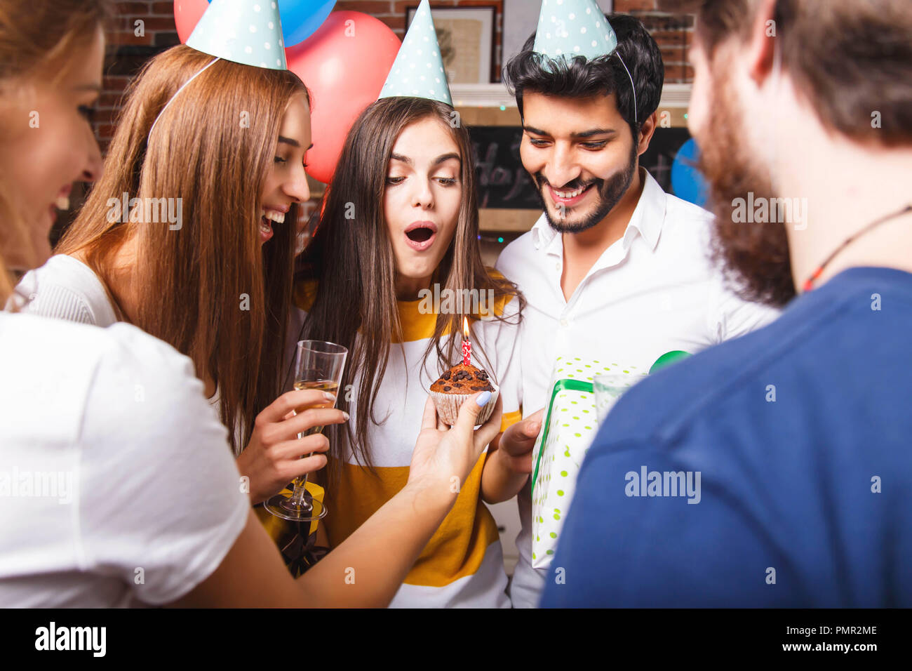 Excited brunette birthday girl ready to blow out candle on birthday cupcake at the birthday party at the kitchen - Stock Image