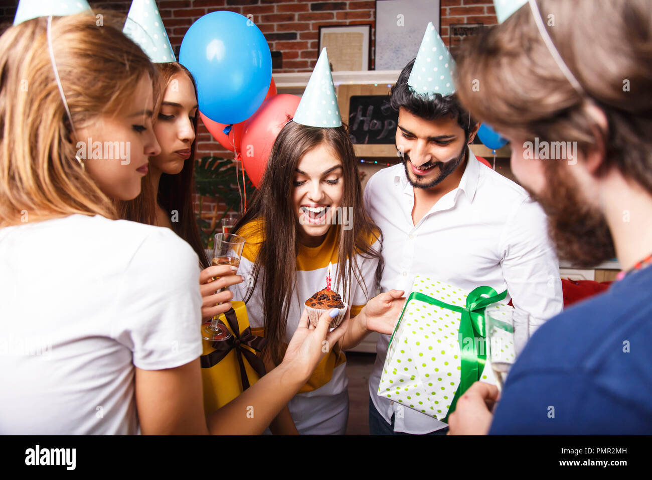 Pretty long hair brunette birthday girl in a party hat celebrating her birthday with the friends - Stock Image