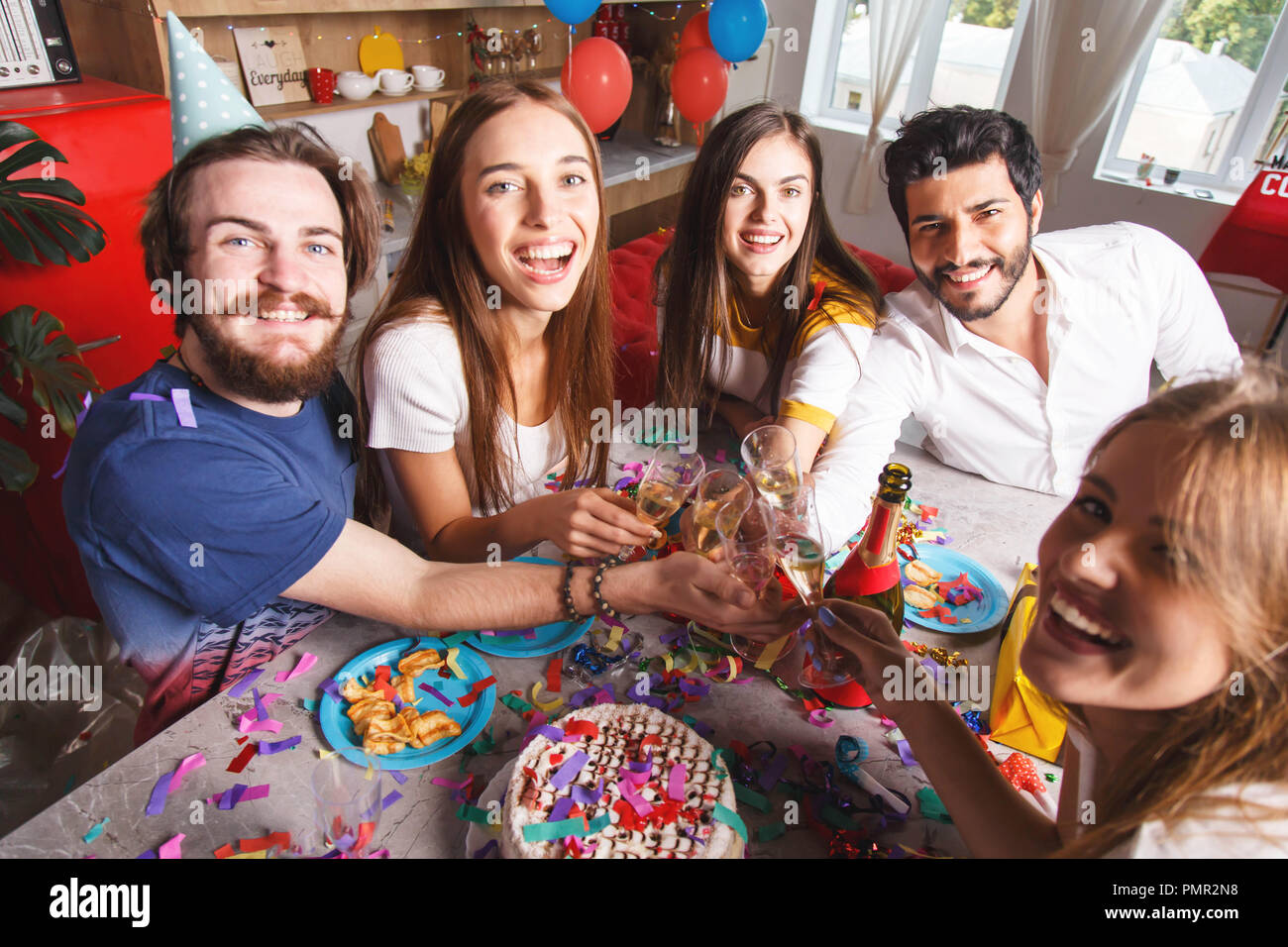 Cheerful best friends laughing and cheers with champagne, they having fun on the birthday party - Stock Image