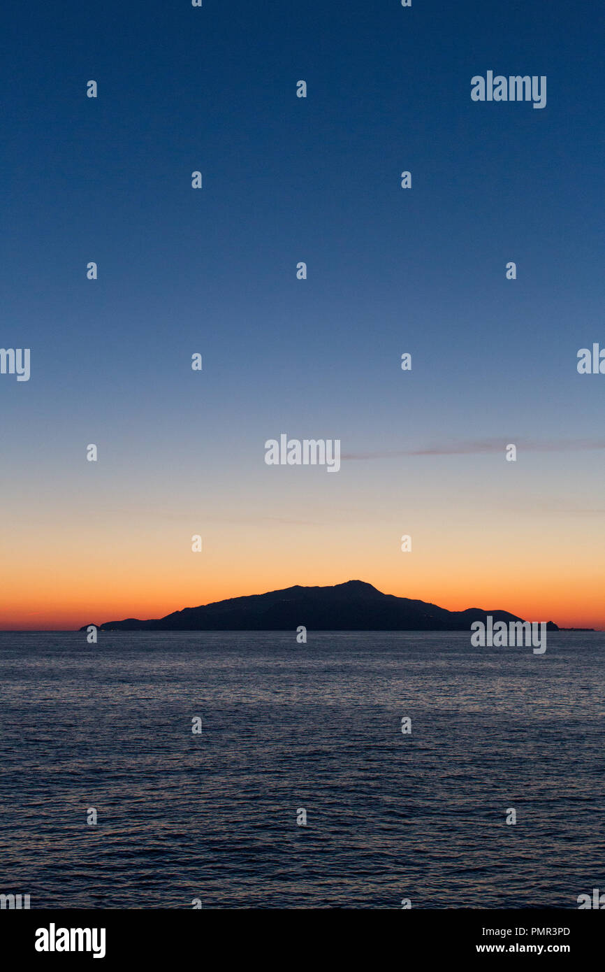 A deserted island, part of the Desertas Islands (Ilhas Desertas) near Madeira, silhouetted in front of a bright orange sunset - Stock Image