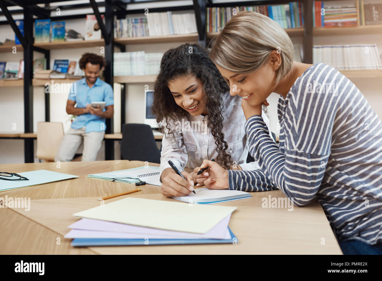 Close up of pair beautiful young multi-ethnic student girls doing homework together, writing essay for presentation, preparing for exams with good mood - Stock Image