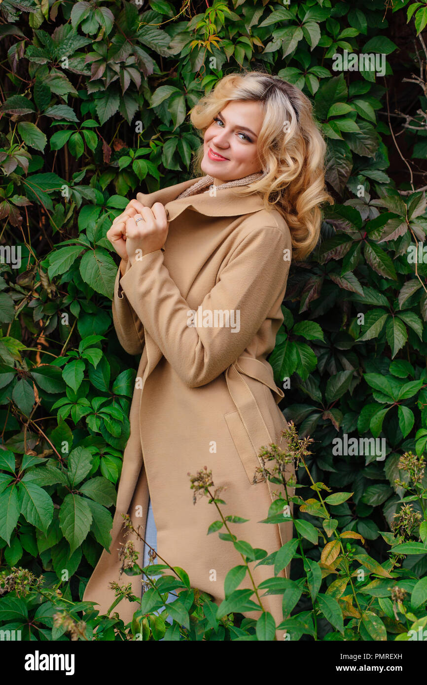 fb6616b51244 Young beautiful woman in sweater and coat stands next to the background of wild  grapes leaves in autumn park