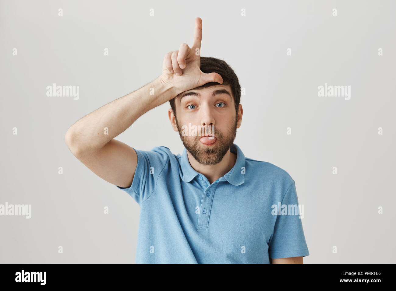 Portrait of cute bearded caucasian guy sticking out tongue and holding hand over forehead in loser gesture, standing against gray background. Impolite man mocking his coworker who lost bet - Stock Image