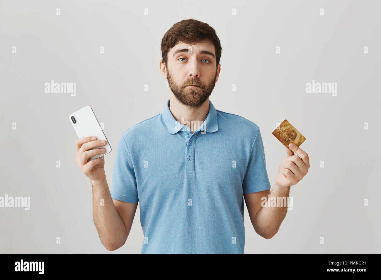 Useless credit card with low balance. Portrait of gloomy displeased young bearded guy holding smartphone and bank card, having problems with payment online, standing over gray background Stock Photo