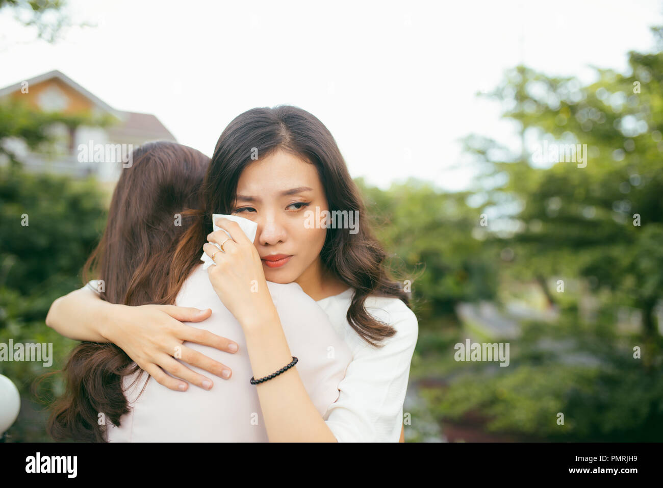 Portrait two women. Sad unhappy young woman being consoled by her friend. Friendship help support and difficult times concept. Human emotions feelings - Stock Image