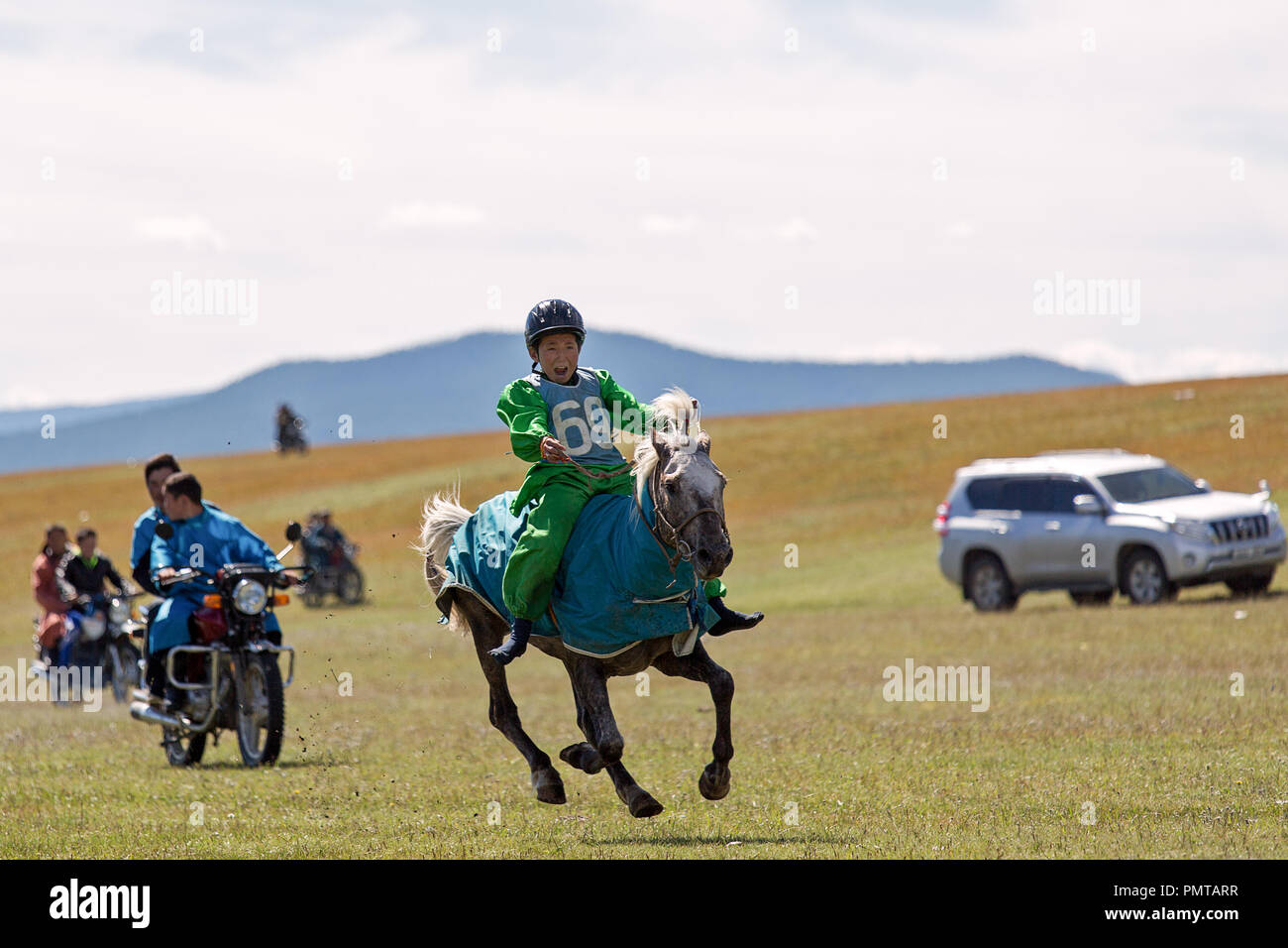 Young boy without shoes is riding a horse participant in the horsemanship competition of the Naadam Festival, Khatgal, Mongolia - Stock Image
