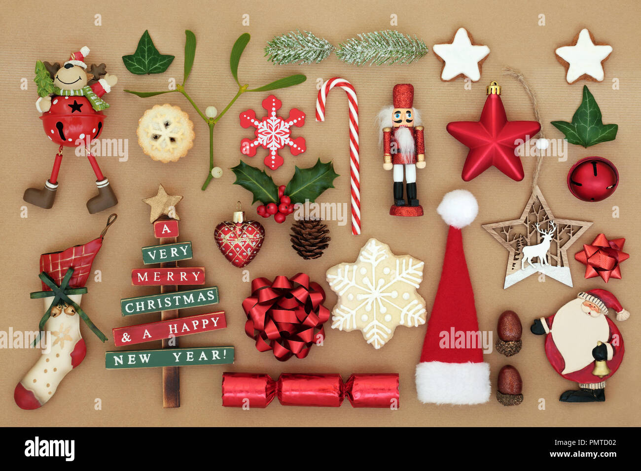 old fashioned christmas tree decorations and baubles with winter flora food and traditional symbols on brown paper background