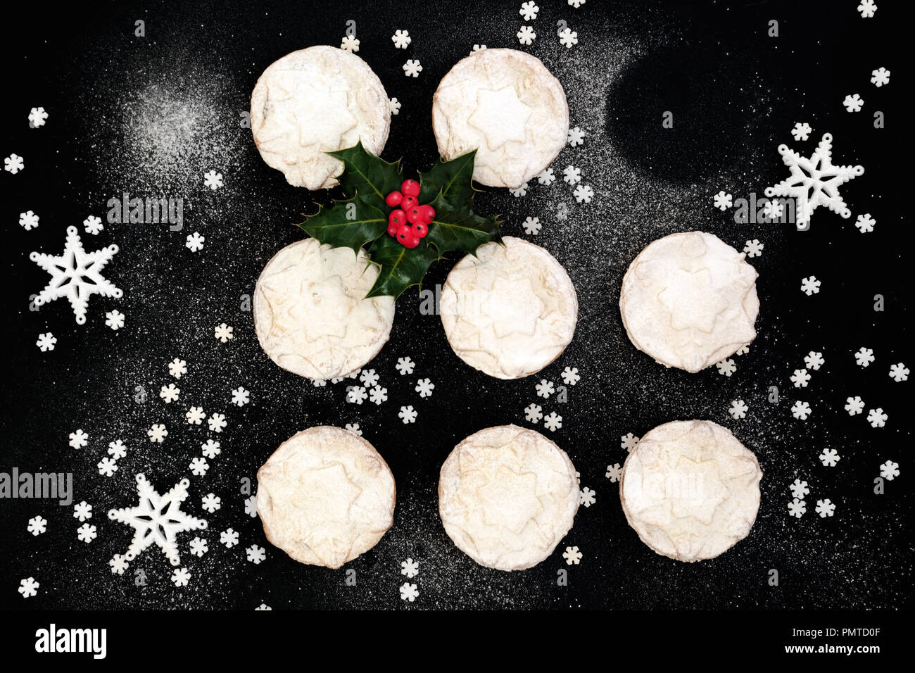 Delicious freshly baked Christmas mince pies with one missing, holly berry leaf sprig, star decorations and icing sugar dusting on black background. T - Stock Image