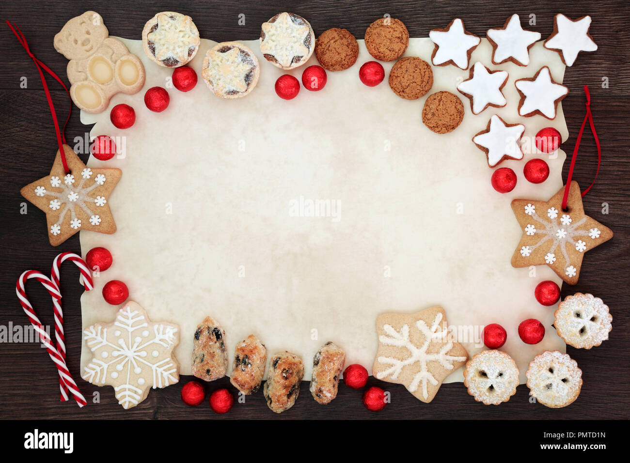Christmas biscuit background border with delicious homemade biscuits, candy canes, cakes and foil wrapped chocolates on parchment paper on rustic oak  - Stock Image