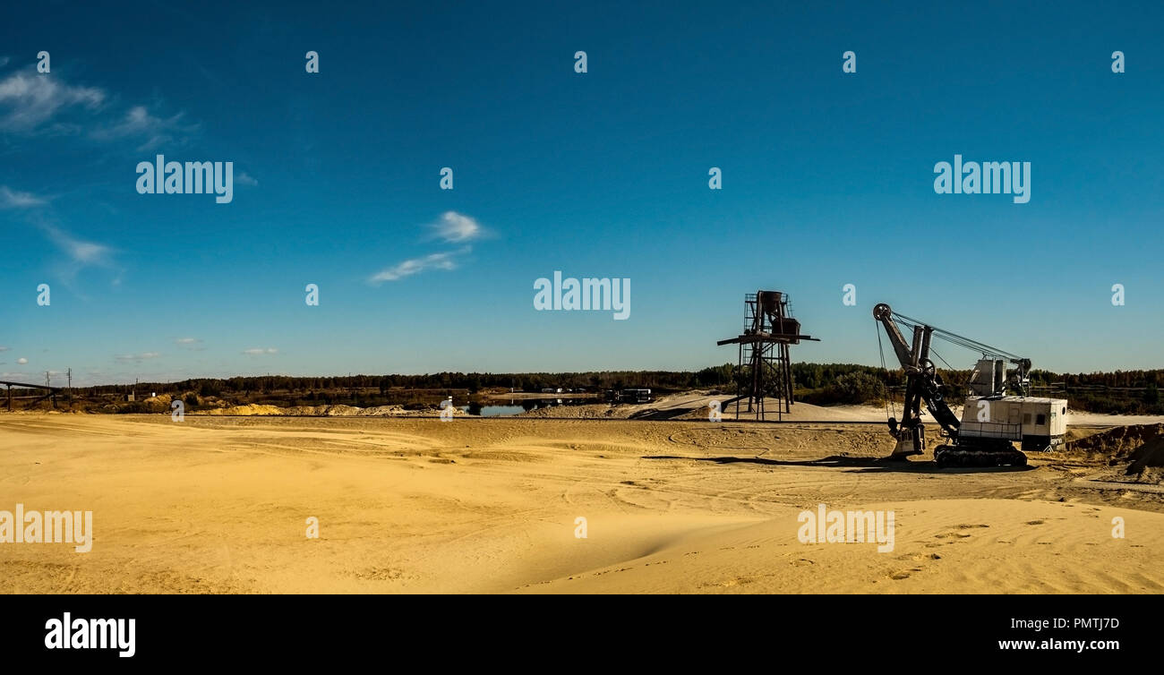 Panoramic view of sand quarry, mining of yellow construction sand, pumping sand from a nearby pond with help of powerful pumps, post-apocalyptic lands - Stock Image