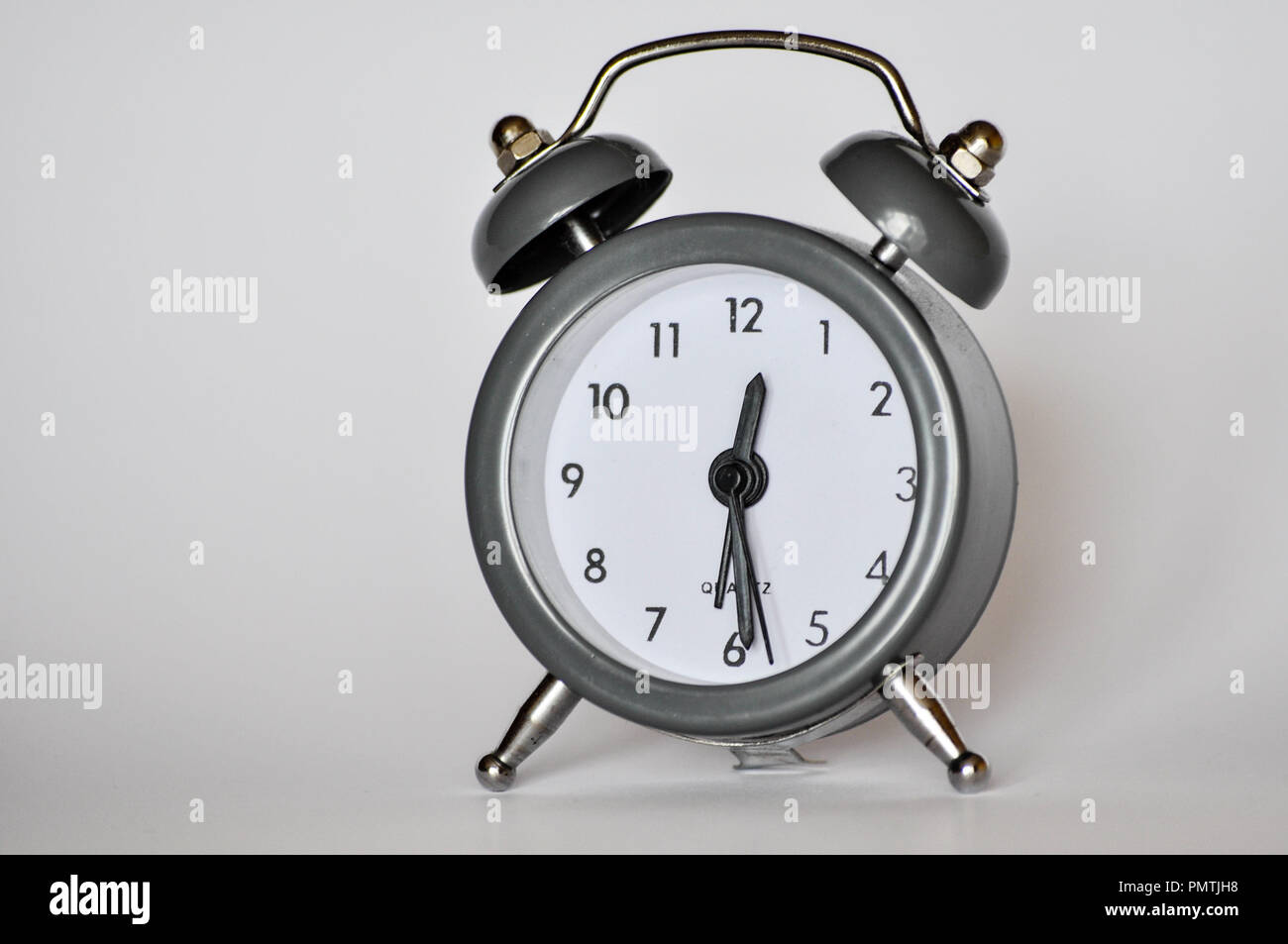 Little, vintage alarm clock showing current hour on a grey background - Stock Image