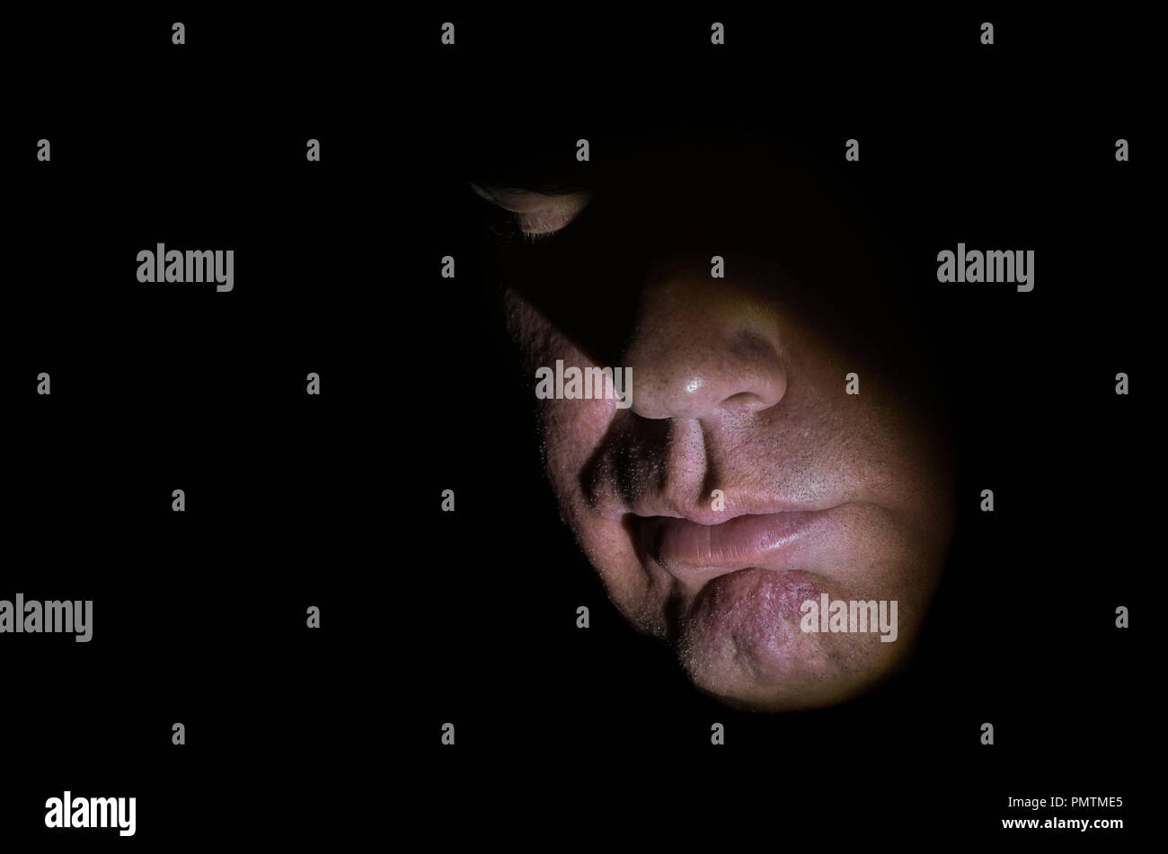 Model released closeup image of middle aged Caucasian man's face, partially lit with moody lighting & eyes closed, showing nose & mouth, looking down. - Stock Image