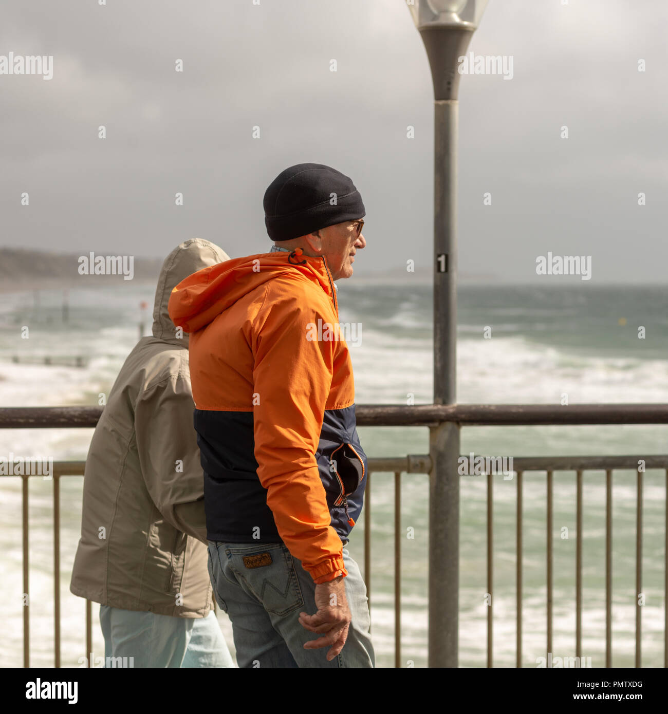 Boscombe, Bournemouth, Dorset, England, UK, September 2018, Weather: Storm Ali, the first named storm of the autumn, brings strong winds gusting to over 50mph to the south coast early afternoon. A couple walking on the pier are dressed for the conditions. - Stock Image