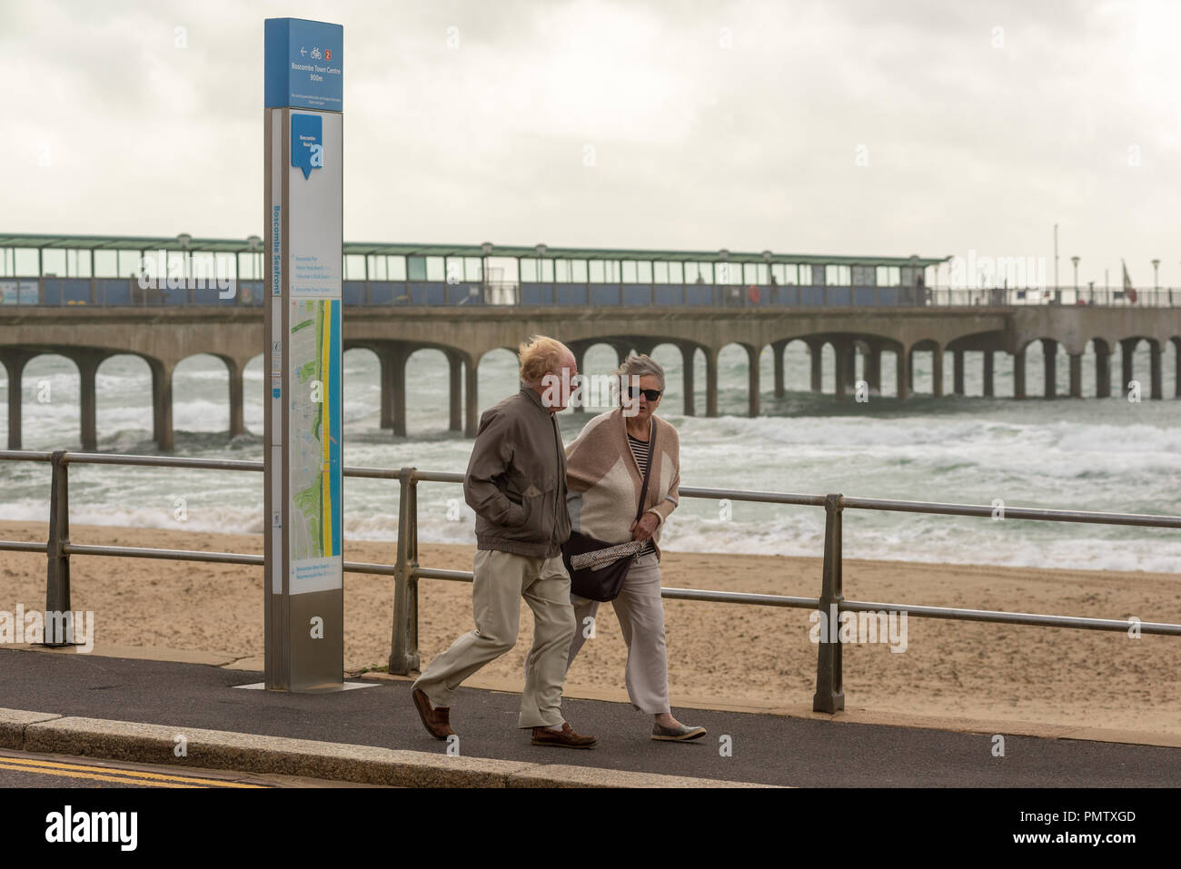Boscombe, Bournemouth, Dorset, England, UK, September 2018, Weather: Storm Ali, the first named storm of the autumn, brings strong winds gusting to over 50mph to the south coast early afternoon. A couple walking along the promenade are blown by the wind. - Stock Image